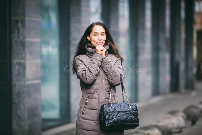 The girl warms her hands in front of her face. The woman froze and sighed with her hands to warm them. Girl on the background of royalty free stock photo