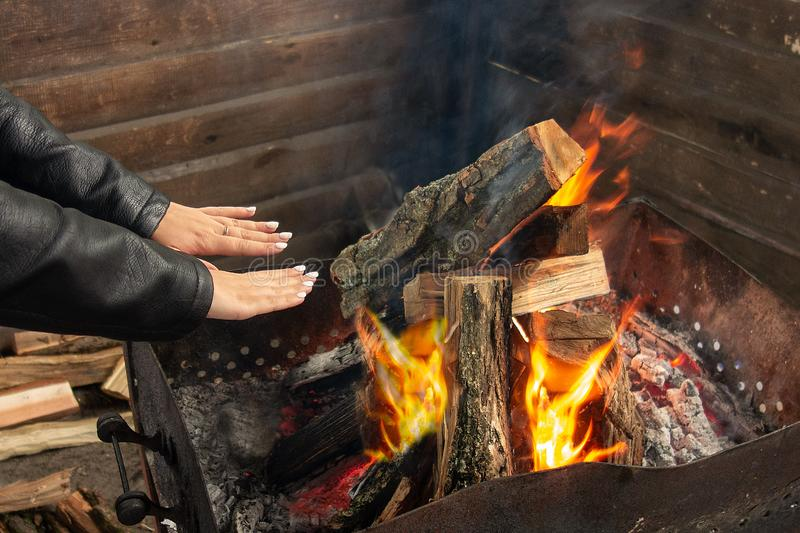 Girl warms up near open fire. Woman holds hands above flame to toast herself. Burning woods logs and charcoal are in barbecue. Grill stock image