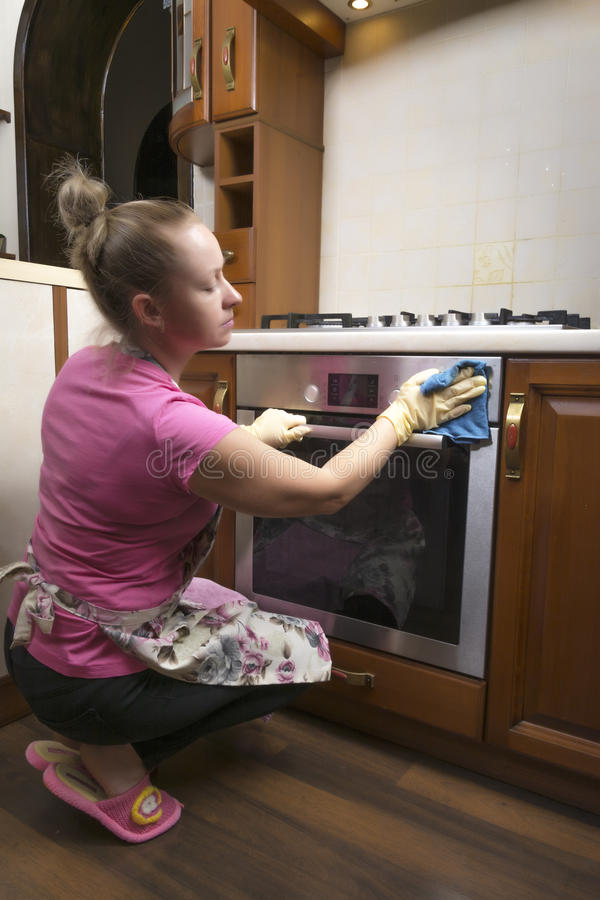 The girl washes the oven in the kitchen. royalty free stock photo