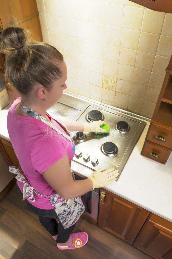 The girl washes the stove in the kitchen. stock photo