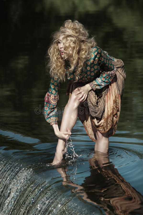 Girl washing her feet in the river water stock photo