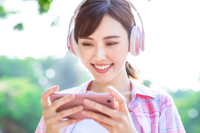 Girl watch video on phone. Young asian girl watch video on her smart phone stock images