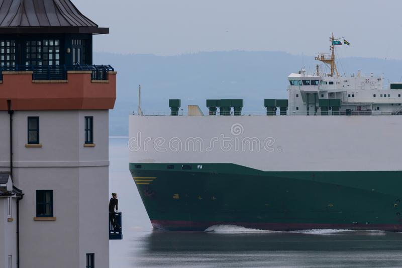 Girl watches transport ship pass a house. A girl watches a car transport ship pass by on the estuary stock photo