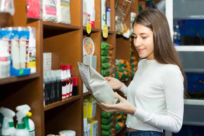 Girl watching dry food in pet store. Smiling young woman watching dry food in pet store stock images