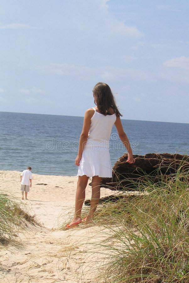 Girl watching friend on beach stock images