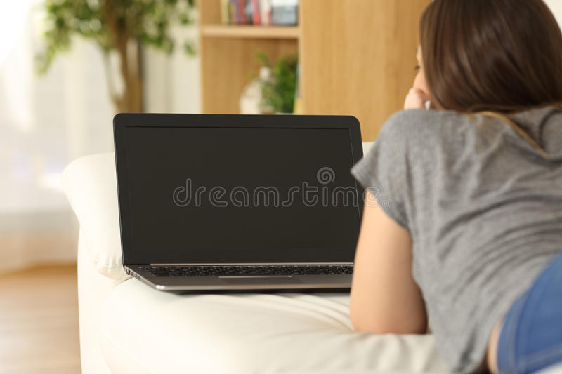 Girl watching media in a laptop showing screen. Rear view of a girl watching media content in a laptop showing a blank screen lying on a couch in the living room royalty free stock photography
