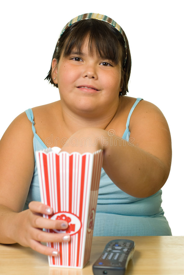 Girl Watching Movie. A young girl watching a movie and eating popcorn royalty free stock images