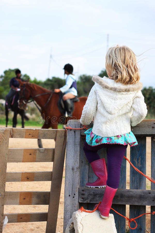 Girl watching a riding lesson stock photos