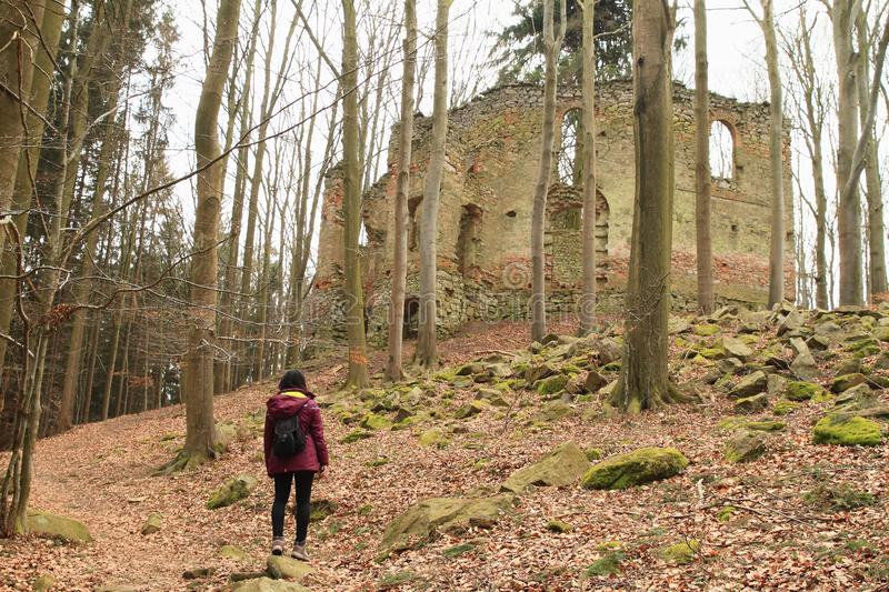 Girl watching ruins of the chapel of St. Mary Magdalene. Young woman with black tourist backpack watching ruins of the chapel of St. Mary Magdalene in forest on royalty free stock photography