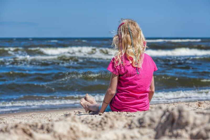Girl watching the seawaves. Little girl sitting at seashore watching waves stock image