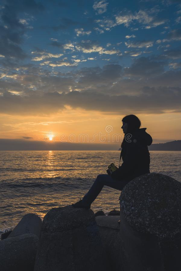 A girl watching a sunrise over the sea in Varna. royalty free stock image