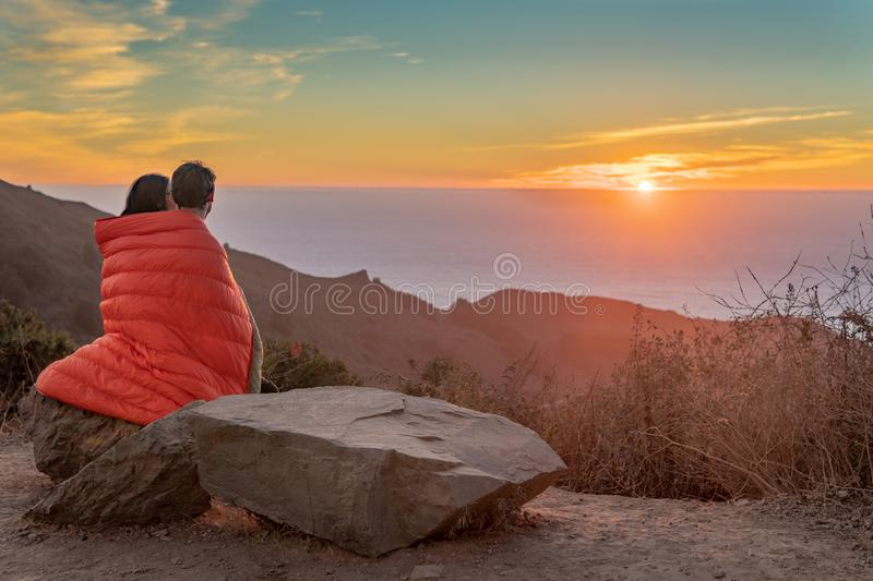 Girl watching Sunset while Draped in blanket royalty free stock photography