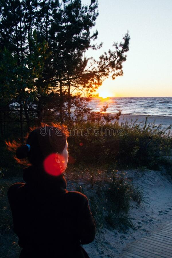 Girl watching the sunset stock image