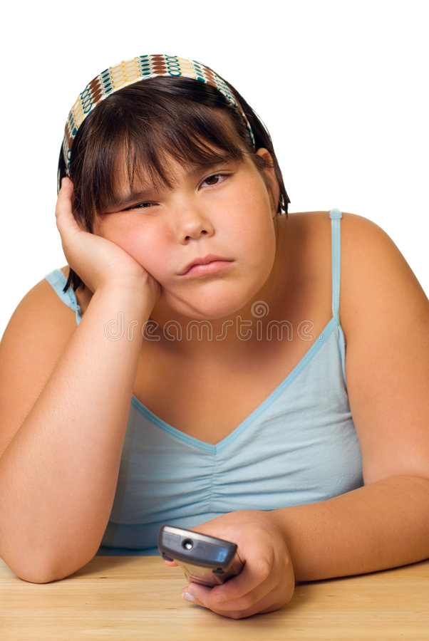 Girl Watching Television. A caucasian girl watching television and holding the remote control royalty free stock photography