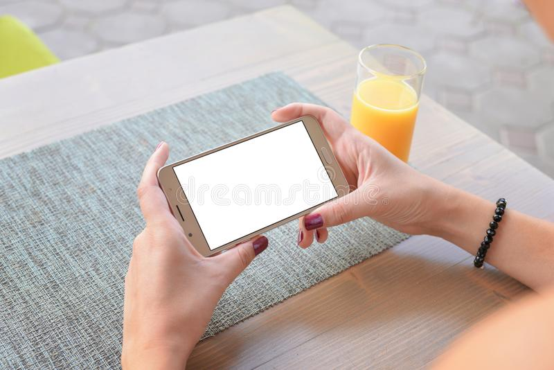 Girl watching video or play game on mobile phone in horizontal position stock image