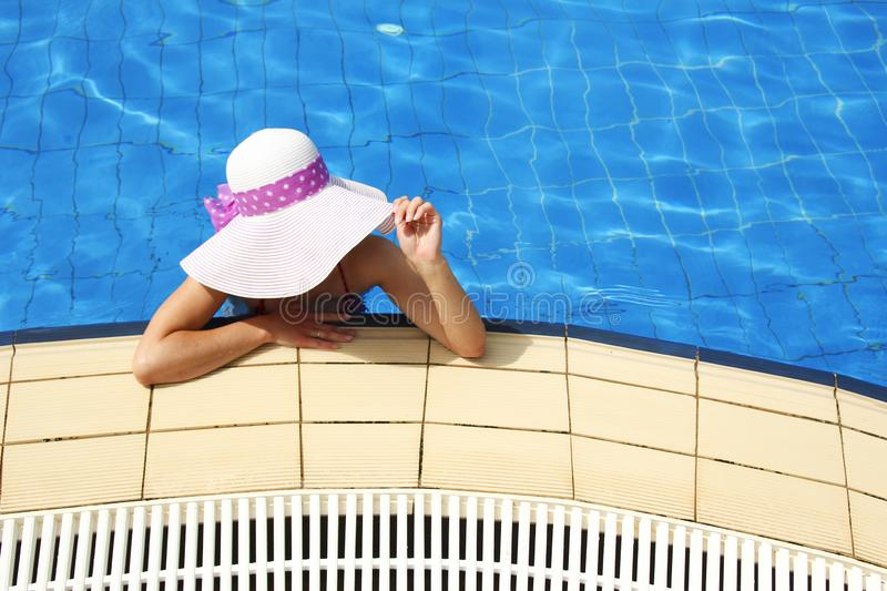 Girl in the water basin. Girl with a hat in the water basin royalty free stock photo