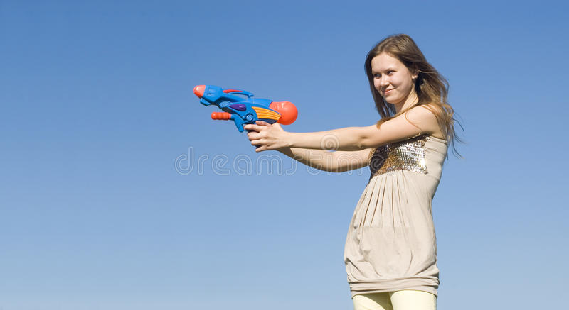 Girl with a water pistol. Holds his hands at gunpoint royalty free stock images