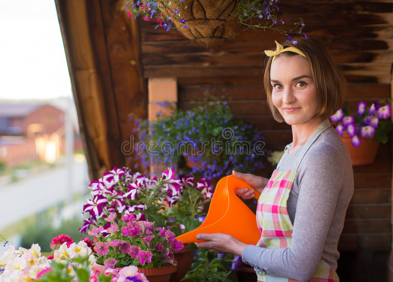 Girl watering flowers. On balcony royalty free stock photography