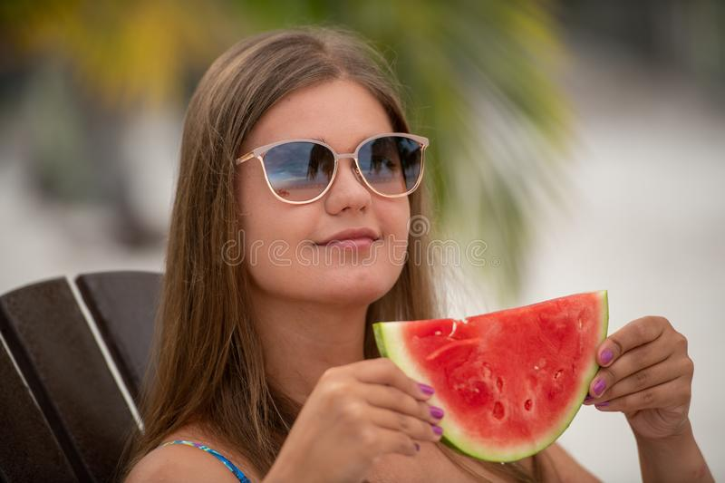 Girl with watermelon under palm tree. Young pretty blonde woman on the beach under palm trees eats watermelon royalty free stock photo