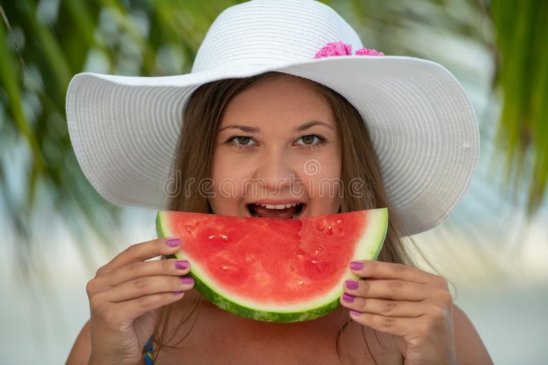 Girl with watermelon. Young pretty blonde woman on the beach under palm trees wears hat and eats watermelon stock photography