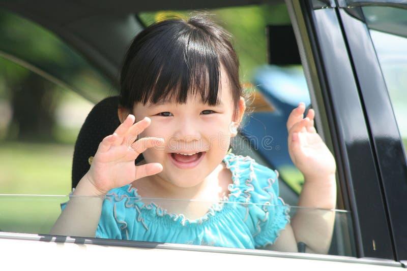 Girl waving goodbye in a car. stock photos