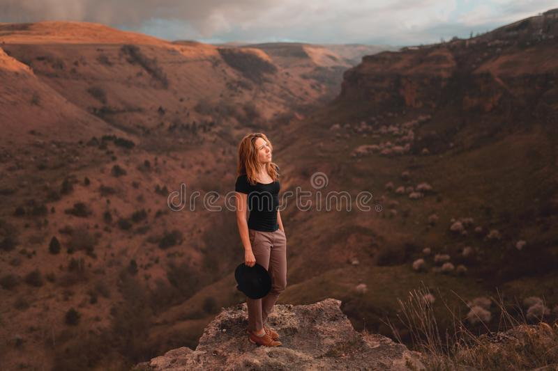 Girl waving her hat with her back facing the valley with mountains. aunset Canyon national park stock image