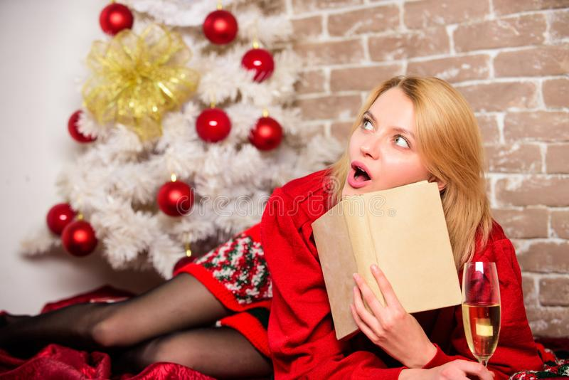 Girl wear red dress sit near christmas tree. Woman hold glass champagne and book. Girl relax near christmas tree. Lady. Celebrate christmas alone. Winter stock photo