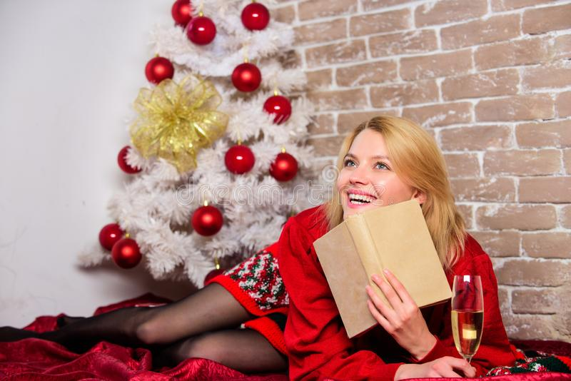 Girl wear red dress sit near christmas tree. Woman hold glass champagne and book. Winter holidays concept. Girl relax. Near christmas tree. Lady celebrate stock images