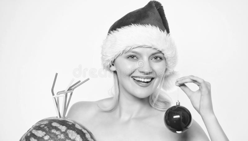 Girl wear santa hat hold ornament ball drink watermelon cocktail. Vitamin nutrition. Winter fruit guide. Woman enjoy royalty free stock images
