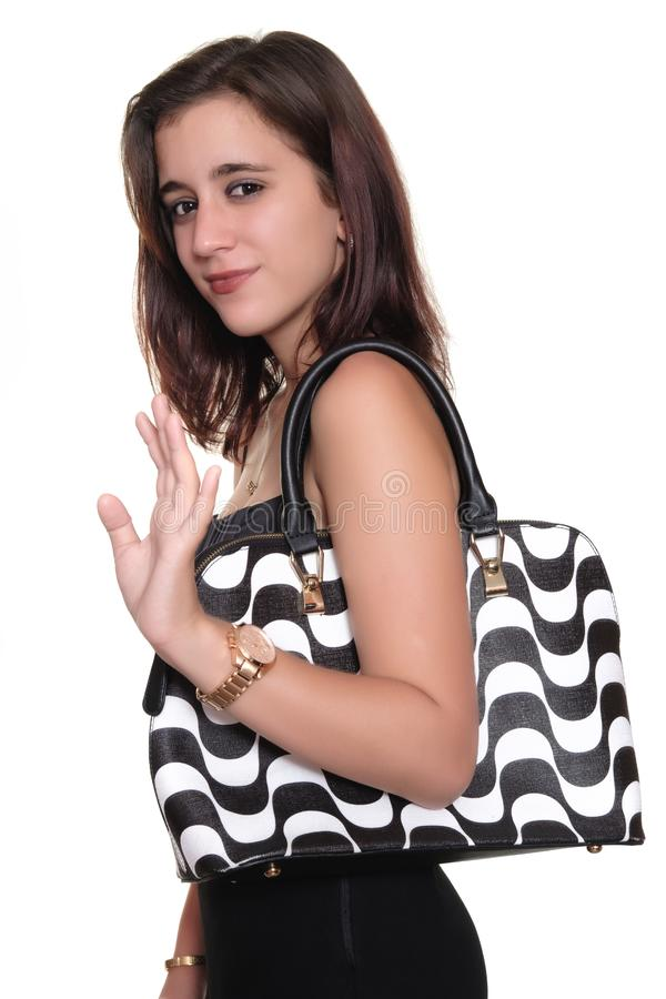 Girl wearing a black dress and a purse smiling and waving goodbye royalty free stock photos