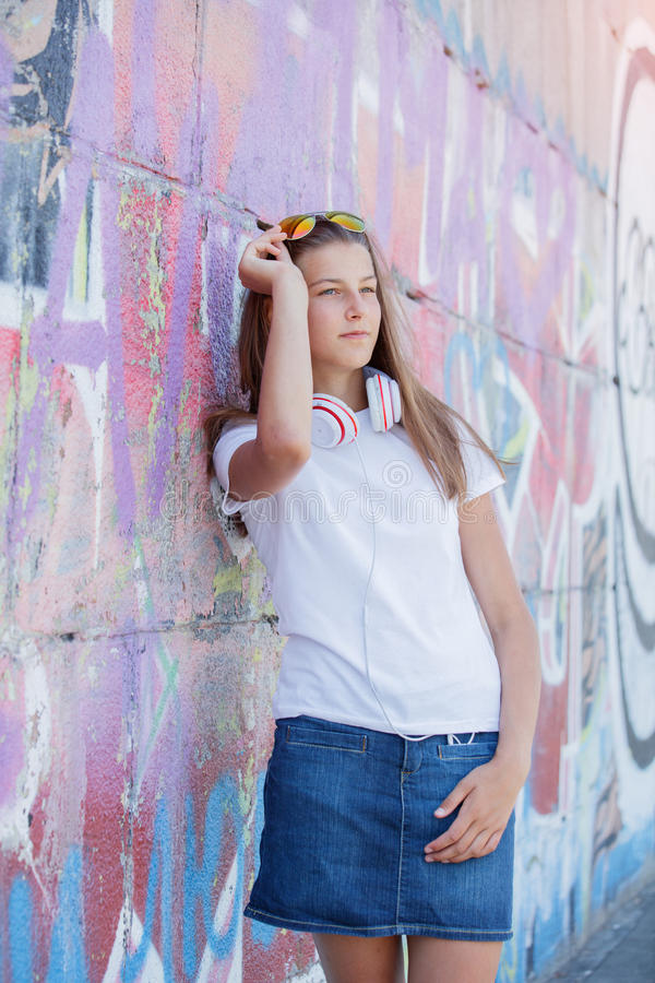 Girl wearing blank white t-shirt, jeans posing against rough street wall stock photo
