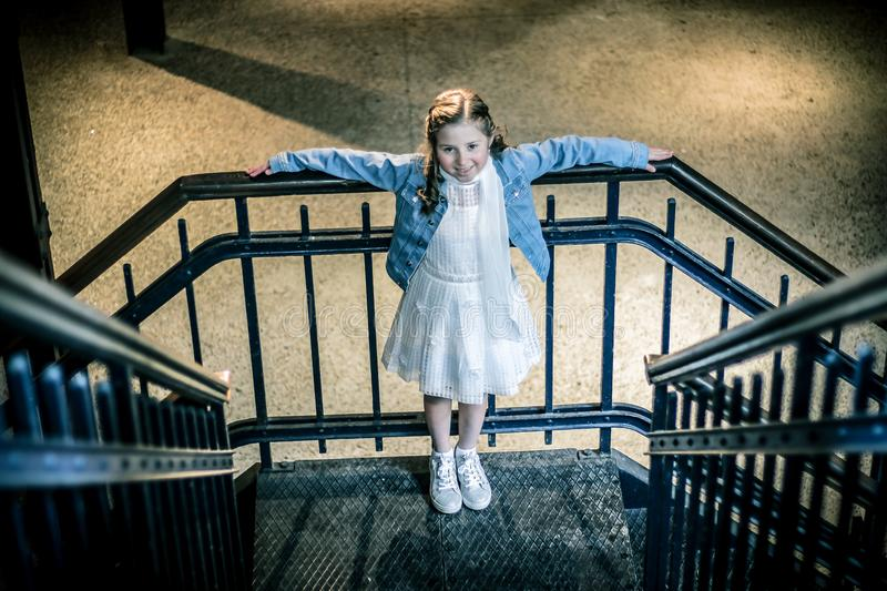 Girl Wearing Blue Jacket and White Dress Standing on Railings during Night Time royalty free stock photo