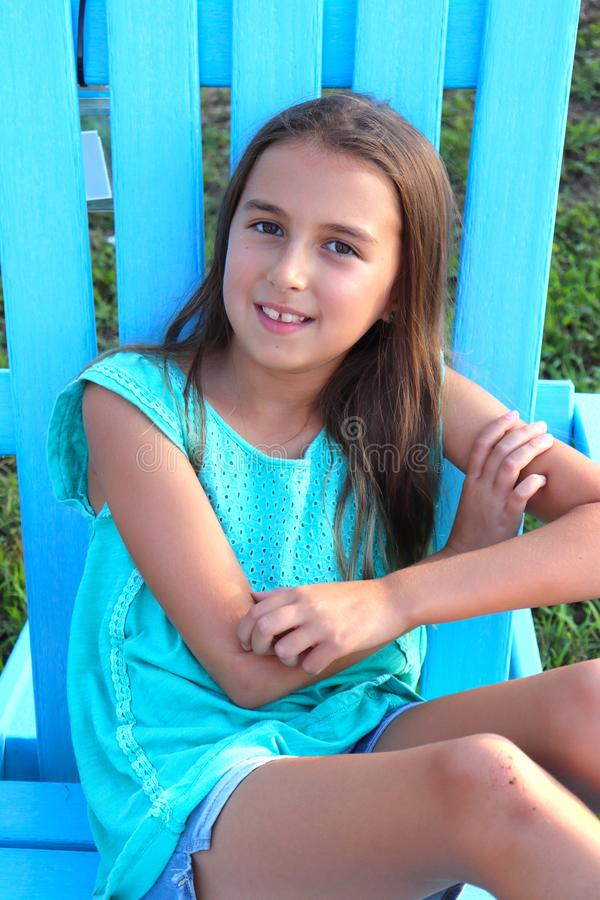 Girl Wearing Blue Sits in Big Blue Outdoor Chair stock image