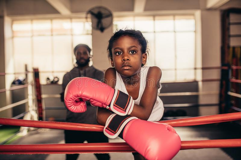 Girl wearing boxing gloves standing near a boxing ring. Confident looking boxing kid standing inside a boxing ring with her coach in the background. Girl wearing royalty free stock image
