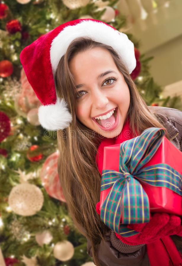 Girl Wearing A Christmas Santa Hat with Bow Wrapped Gift In Front of Decorated Tree stock image