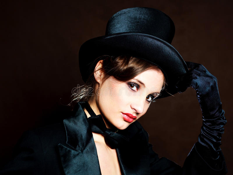 Girl wearing a cylinder hat. Beautiful young brunette woman wearing a black cylinder hat, a smoking jacket and a butterfly bow tie stock images
