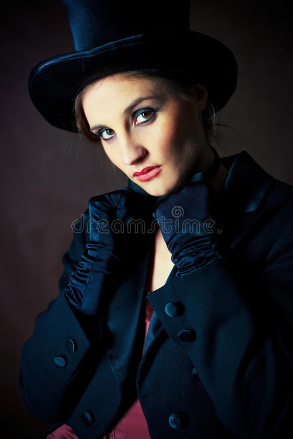 Girl wearing a cylinder hat. Beautiful young brunette woman wearing a black cylinder hat, a smoking jacket and a butterfly bow tie stock image