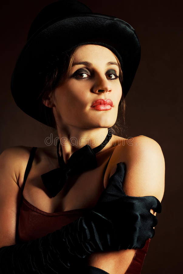 Girl wearing a cylinder hat. Beautiful young brunette woman wearing a black cylinder hat, a smoking jacket and a butterfly bow tie royalty free stock images