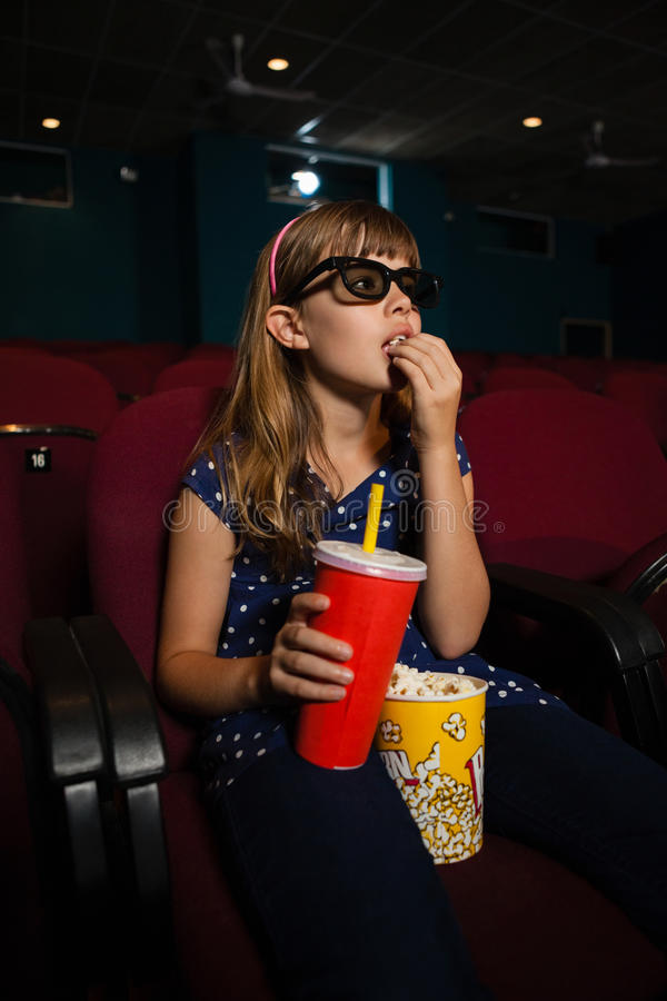 Girl wearing 3D glasses while eating popcorn during movie royalty free stock photos