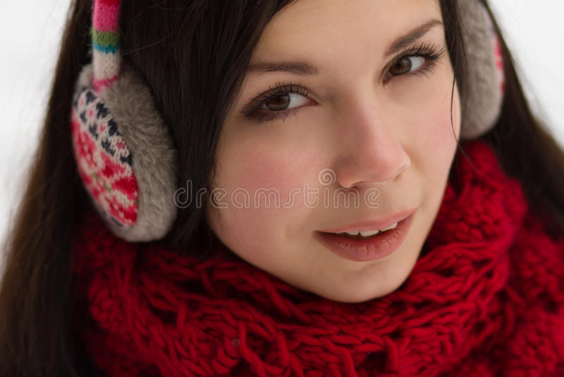 Girl wearing earplugs outdoors in winter stock photo