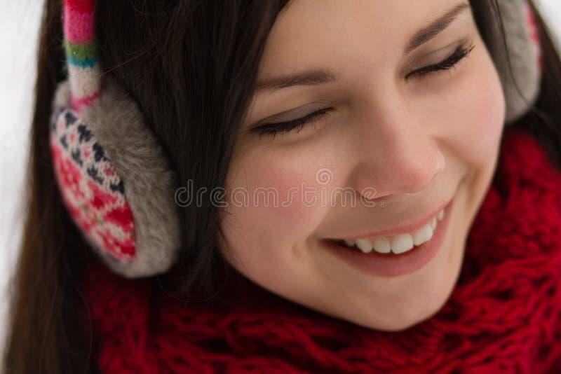 Girl wearing earplugs outdoors in winter royalty free stock photos