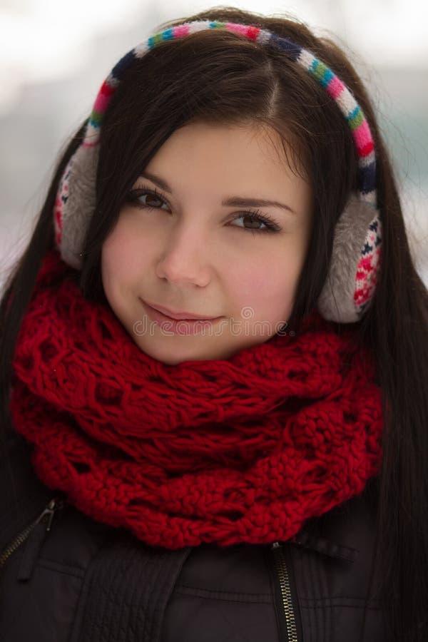 Girl wearing earplugs outdoors in winter royalty free stock image