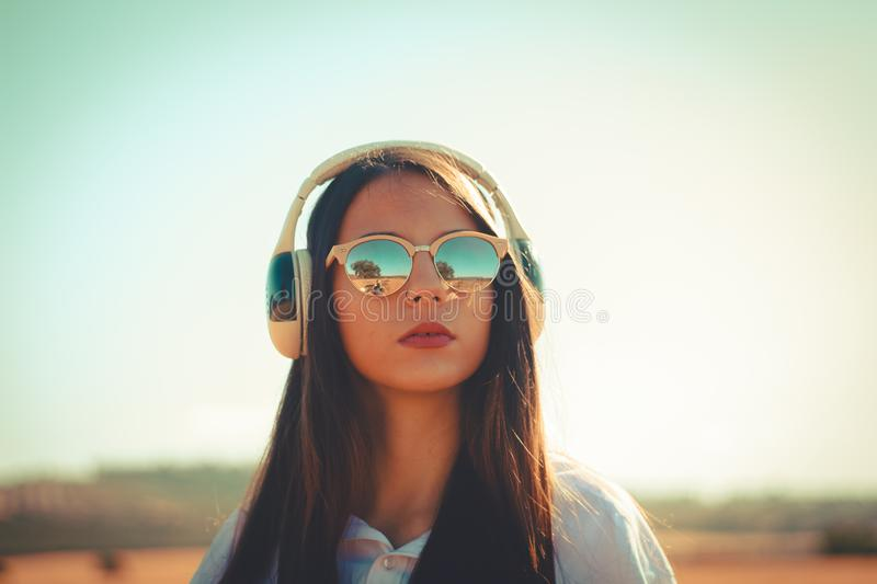 Music lifestyle. Girl wearing fashionable sunglasses and listening music with wireless headphones outdoor stock images