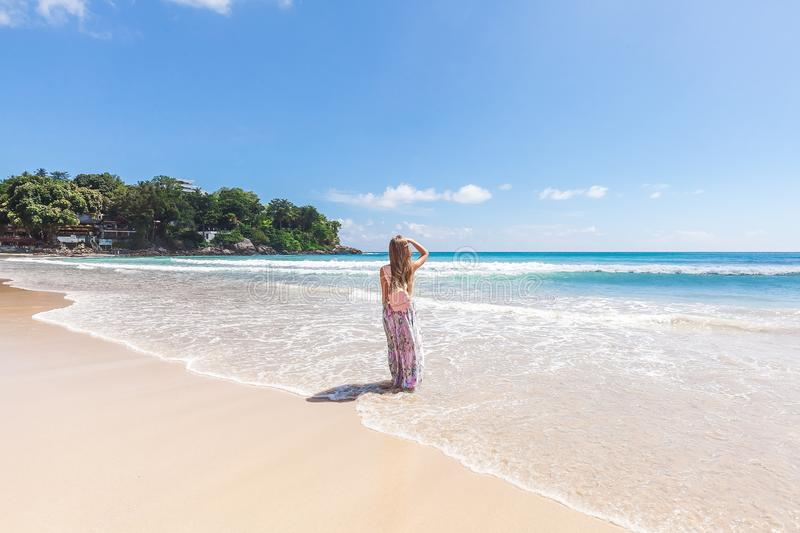 Girl in floral pink maxi skirt walking on the sea shore. Girl wearing floral pink maxi skirt and backpack looking on the sea shore while sky is incredible blue royalty free stock photography