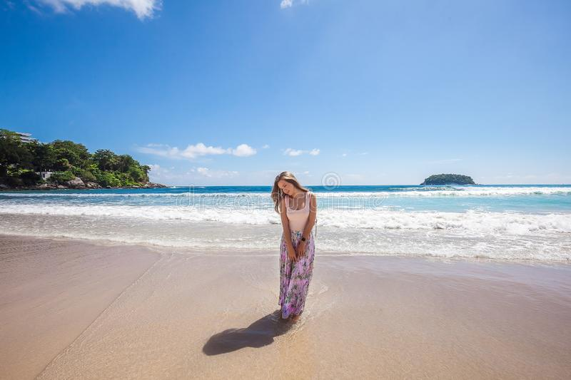Girl in floral pink maxi skirt walking on the sea shore. Girl wearing floral pink maxi skirt walking barefoot on the sea shore while sky is incredible blue stock photography