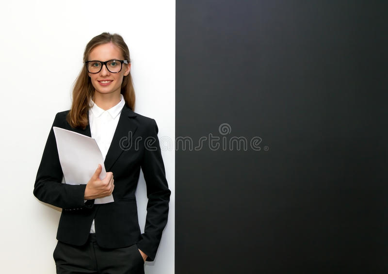 The girl wearing glasses with papers. Costs at a black & white wall royalty free stock image