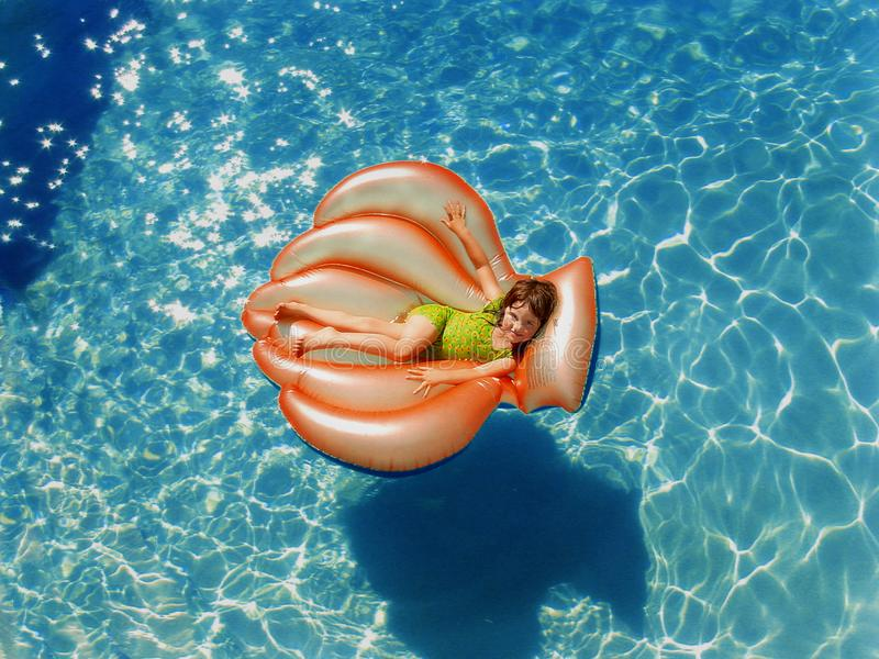 Girl Wearing Green Wet Suit Riding Inflatable Orange Life Buoy on Top of Body of Water stock photos
