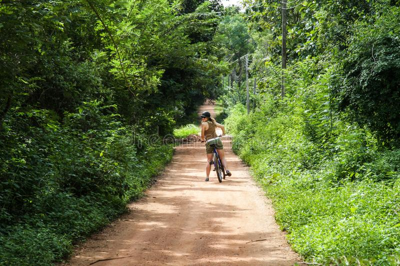 Girl on a bike in Sri Lanka. Girl wearing a hat and sunglasses on a bicycle, looking over her shoulder. Taken in a dirt road in Sri Lanka royalty free stock images