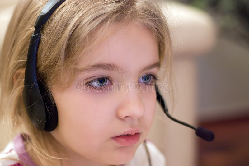 Girl wearing headset. A young girl with headset on, sitting in front of her computer. MY KIDS COLLECTION stock photos