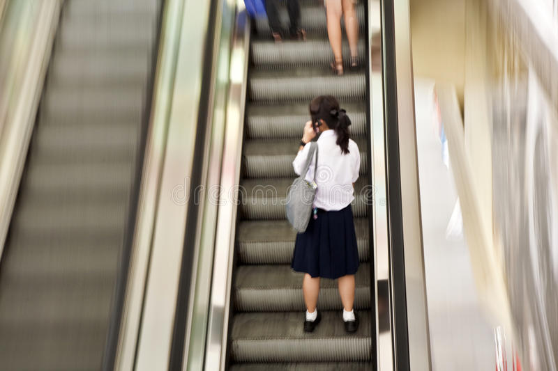 Girl wearing her school uniform on an escalator stock images